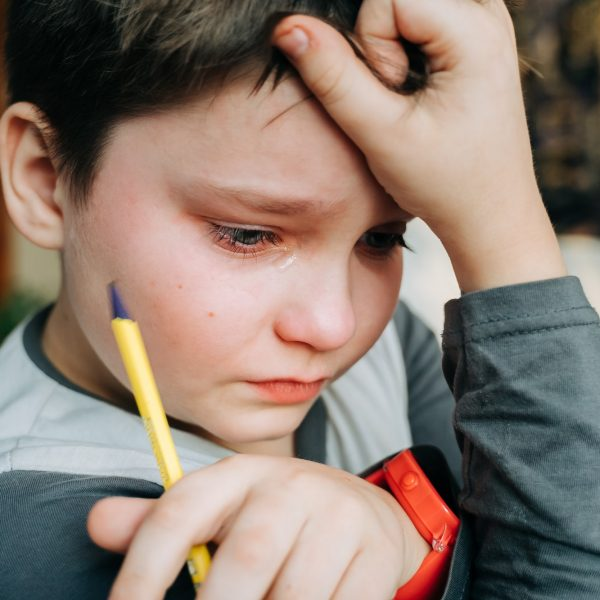 Crying unhappy child boy holding a pen while doing school homework.